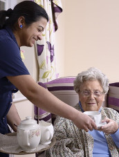 Image of a staff member handing a resident a cup of tea