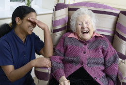 Image of a resident and a member of staff laughing