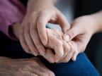 Image of elderly hands being held and comforted